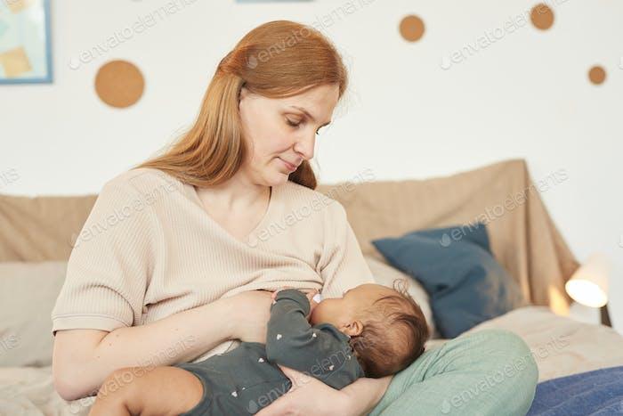 Liebevolle Mutter Stillen Baby auf Bett