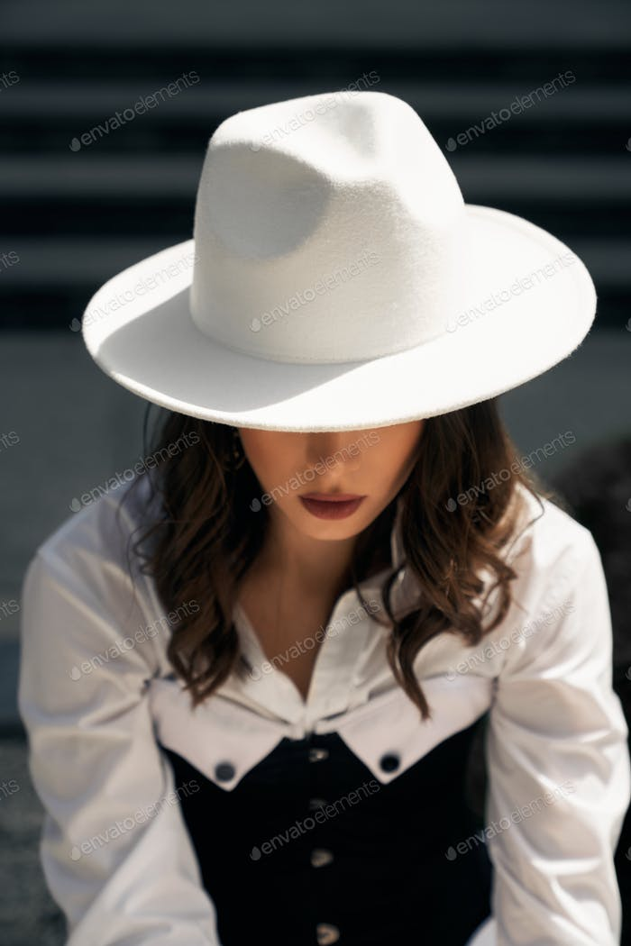 Unrecognizable model wearing hat posing outdoors