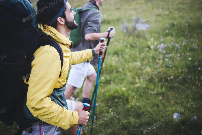 Two man traveling in a mountains staying on footpath relaxing and enjoying the wiew
