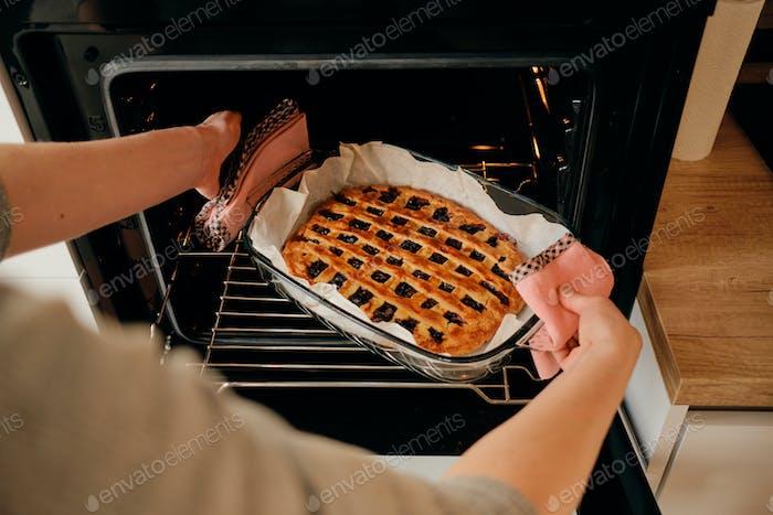 Frau nehmen frisch gebackenen Jem Kuchen aus dem Ofen