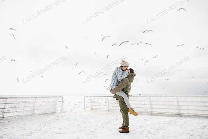 happy couple kissing on winter quay with seagulls