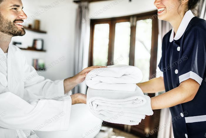 Housekeeper handing over fresh towels
