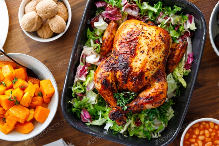 Decorated festive table with whole roasted chicken, salad, pumpkin, beans and walnut.