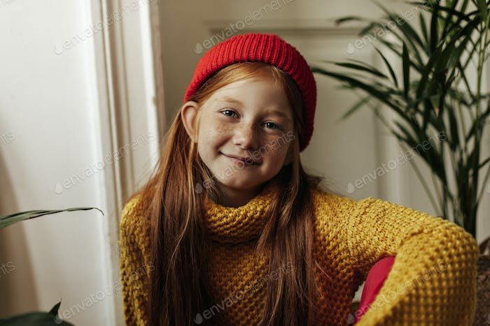Wonderful young girl with foxy hairstyle and freckles in bright red cap and trendy sweater looking