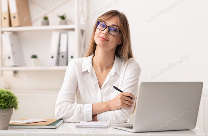 Confident Businesswoman Smiling At Camera Sitting In Modern Office
