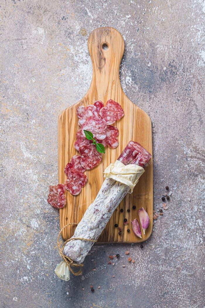 Italienische Salami auf Holzbrett mit Käse und Oliven