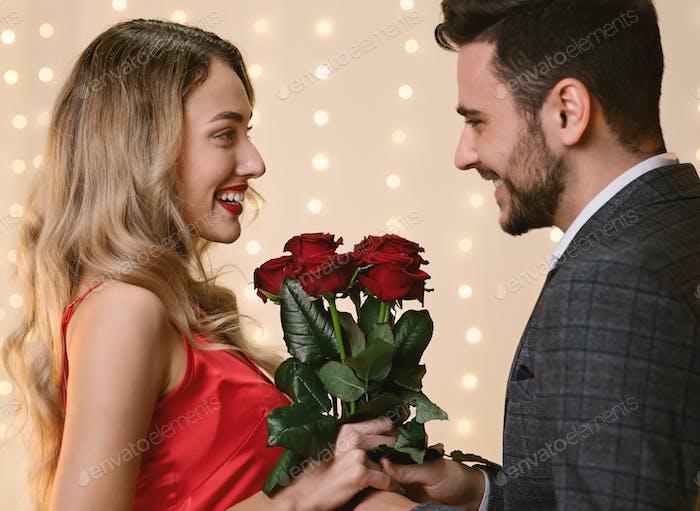 Valentinstag Blumen Liebevolle Mann geben Rosen zu seine glücklich Freundin