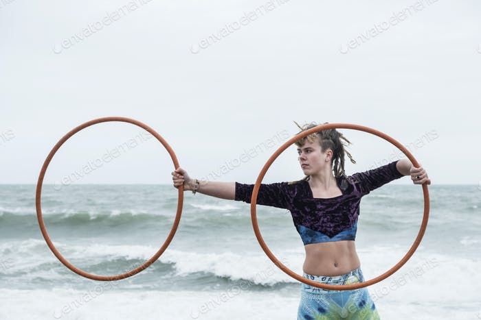Young woman with brown hair and dreadlocks standing by the ocean, balancing two hula hoops.