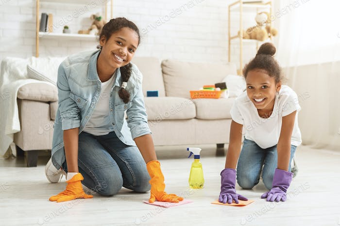 Two adorable girls cleaning carpet at home