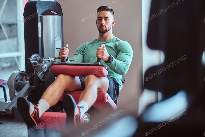 Strong pensive man is sitting on training apparatus in gym and doing legs exercises
