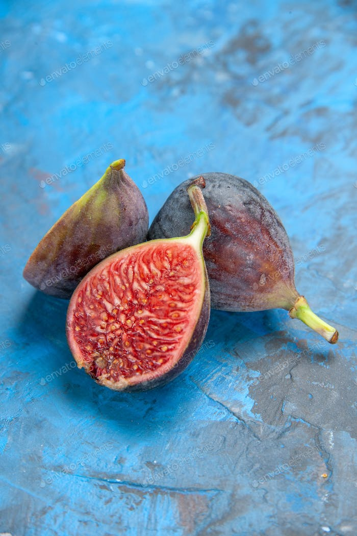 Vertical view of split and full fresh black mission figs on blue background