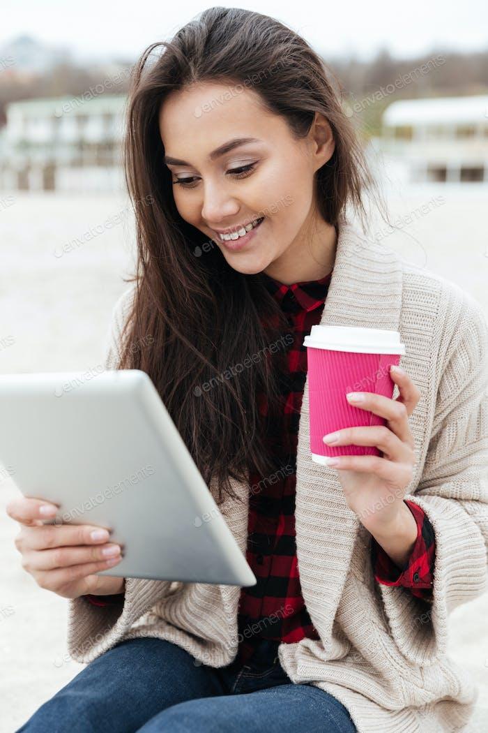 Glückliche kaukasische Dame sitzen im Freien am Strand mit Tablet-Computer