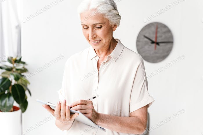 Smiling mature business woman taking notes