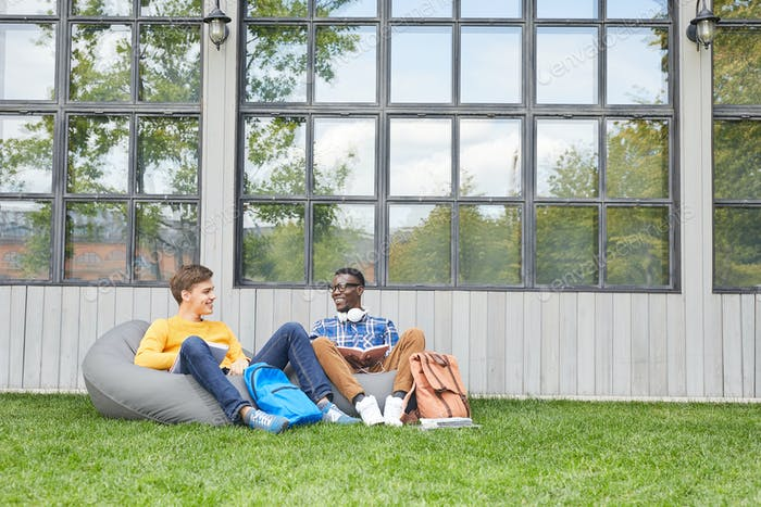 Two Cheerful Students Relaxing Outdoors