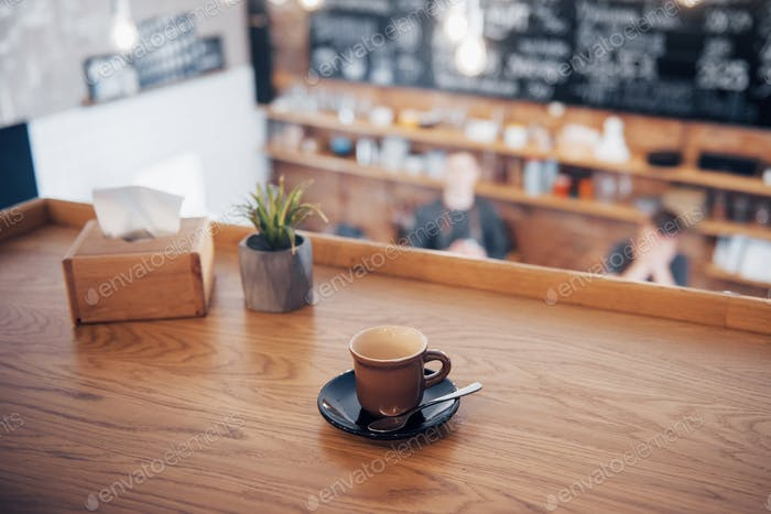 vintage tone of cup of coffee on table in Coffee shop blur background with bokeh image