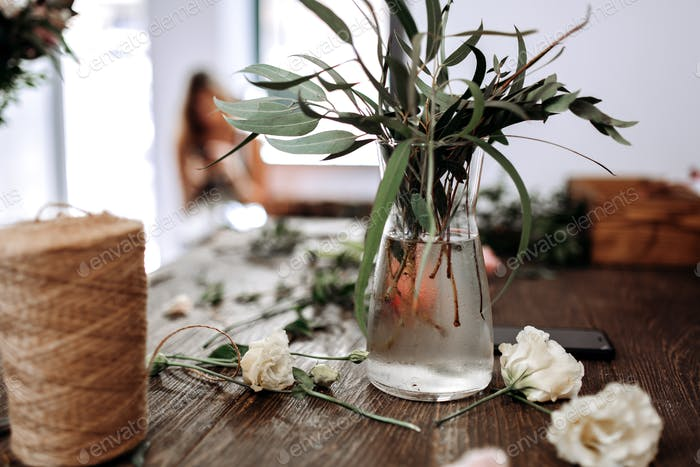 There is a vase with water and branches with green leaves and bobbin of twine on the table of