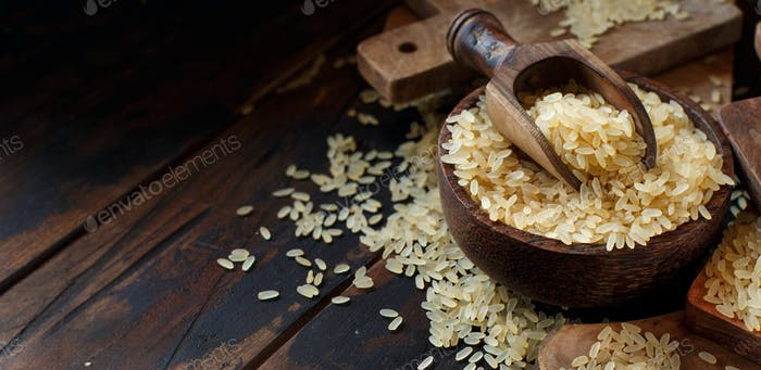 Parboiled rice in a wooden bown with a spoon