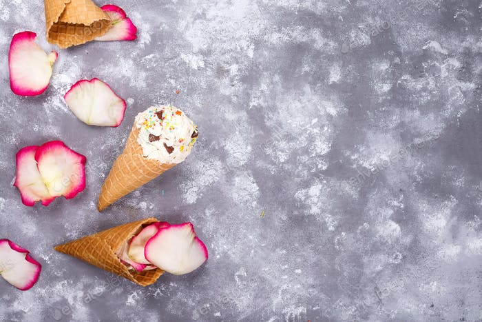 Composition of ice cream waffles with roses petals on a stone background