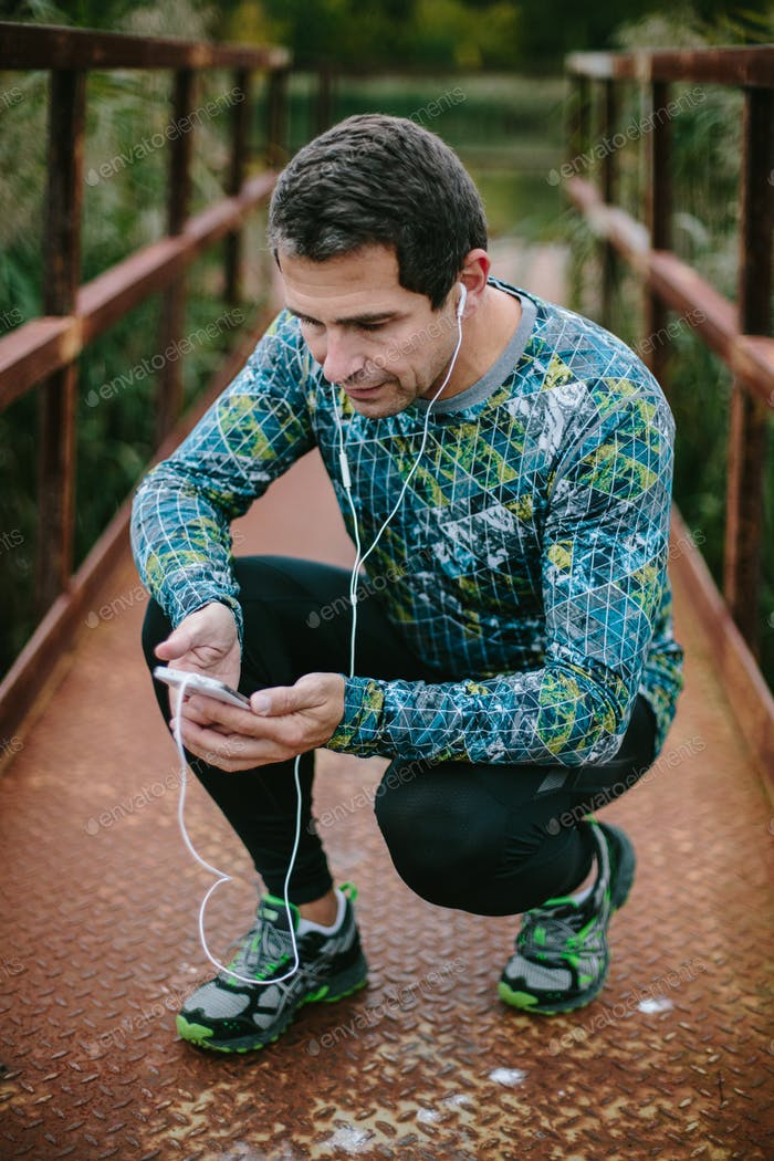 Runner on rusty bridge with smart phone listening music
