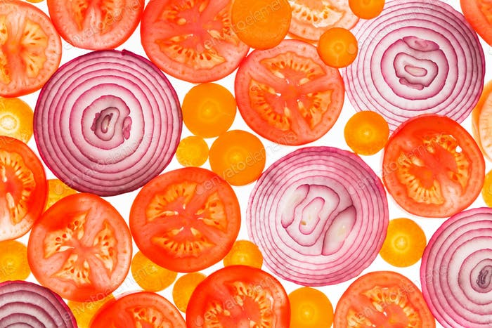 Backlit slices of tomatoes, carrots and onion