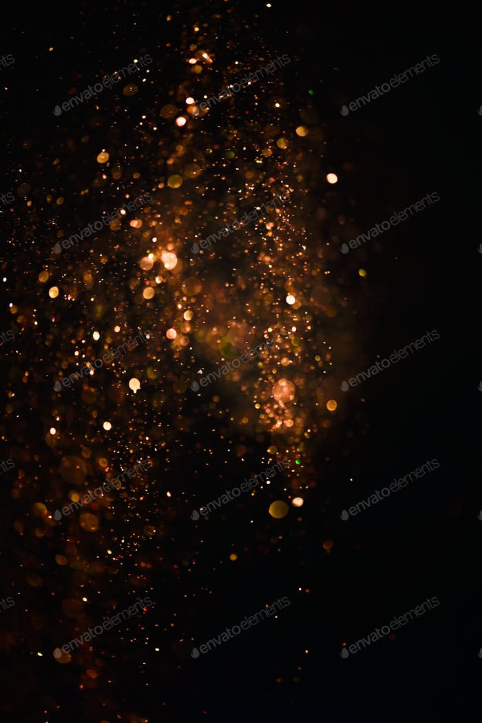 Glitter lights abstract texture. Gold defocused bokeh on a dark background. Card for Birthday