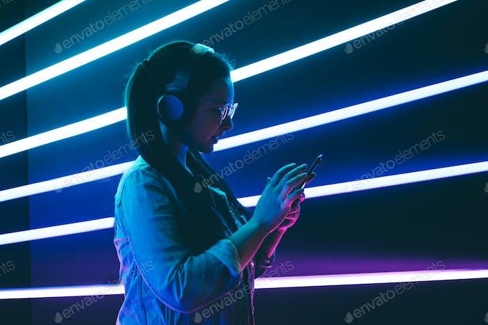 Frau in Kopfhörern hören Musik in Neonlicht mit Telefon auf den Händen.