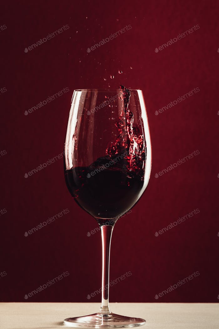 splash of red wine in wineglass standing on tabletop on red