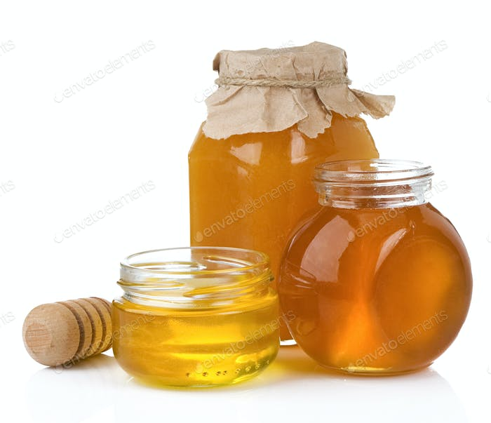 glass jar and pot of honey with stick