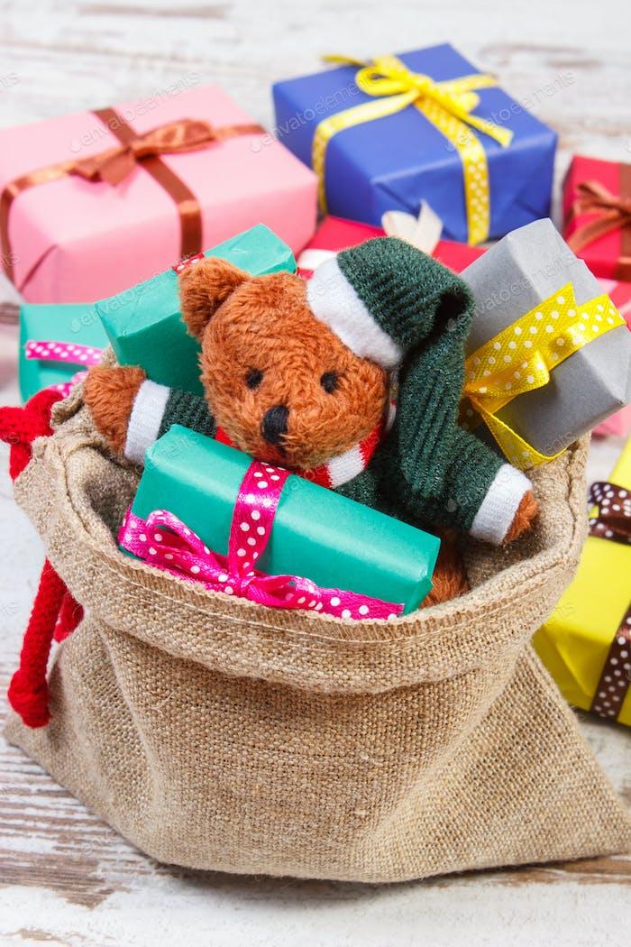 Teddybär mit bunten Geschenken für Weihnachten oder andere Feier