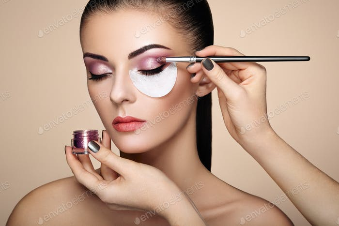 Makeup artist applies eye shadow