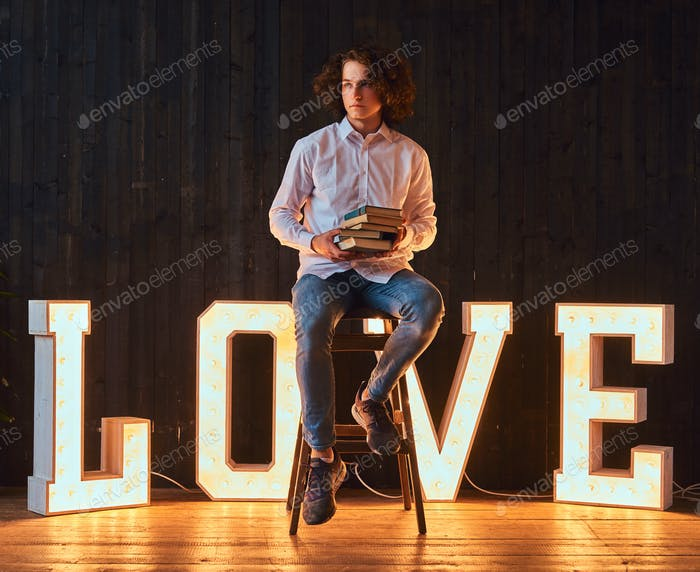Student in a room decorated with voluminous letters with illumination.