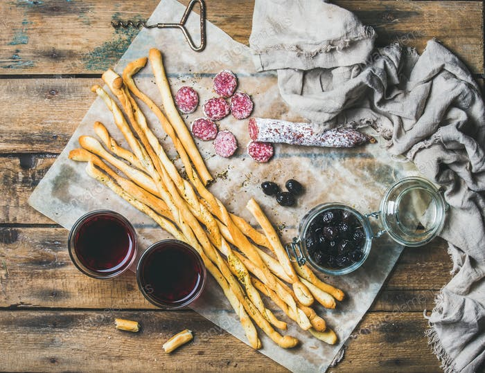 Grissini bread sticks, sausage, olives and red wine, wooden background