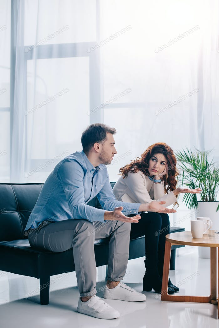Divorcing young couple arguing in psychiatrist office
