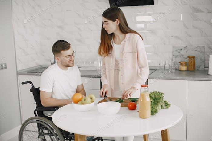 Esposa alentar marido discapacitado sentado en silla de ruedas en la mesa de la cocina