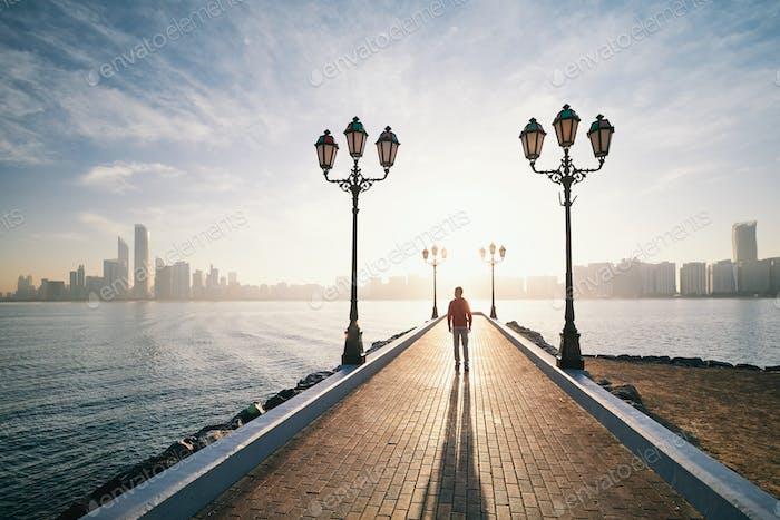 Hombre caminando en la acera contra el horizonte urbano al amanecer