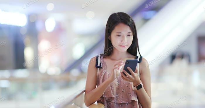 Frau Nutzung des Mobiltelefons und Blick auf die Kamera