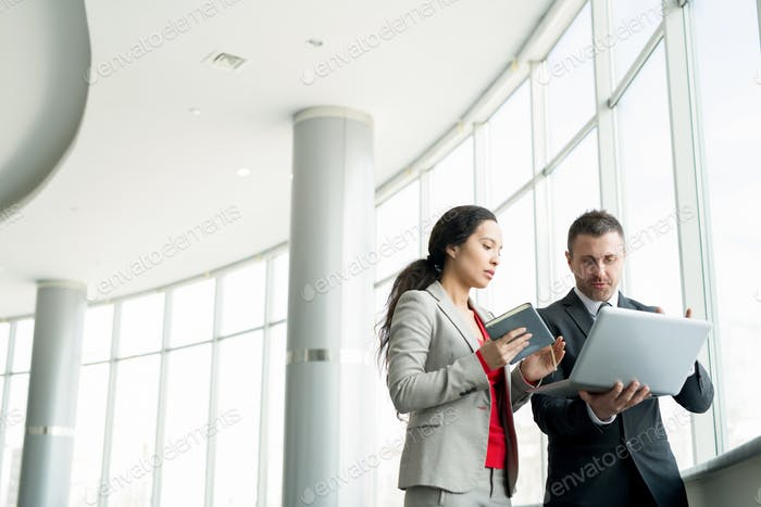 Businesswoman Talking to Colleague by Window