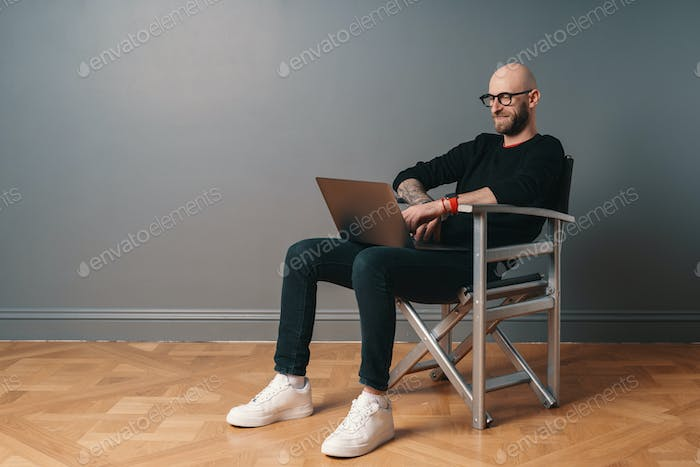 Modern young caucasian man with beard and glasses relaxing while surfing internet on laptop pc
