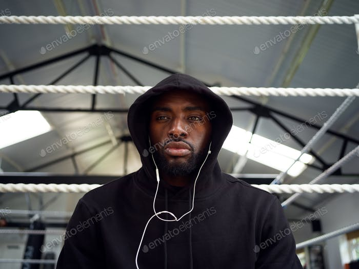 Portrait Of Male Boxer Training In Gym Listening To Music On Headphones In Boxing Ring