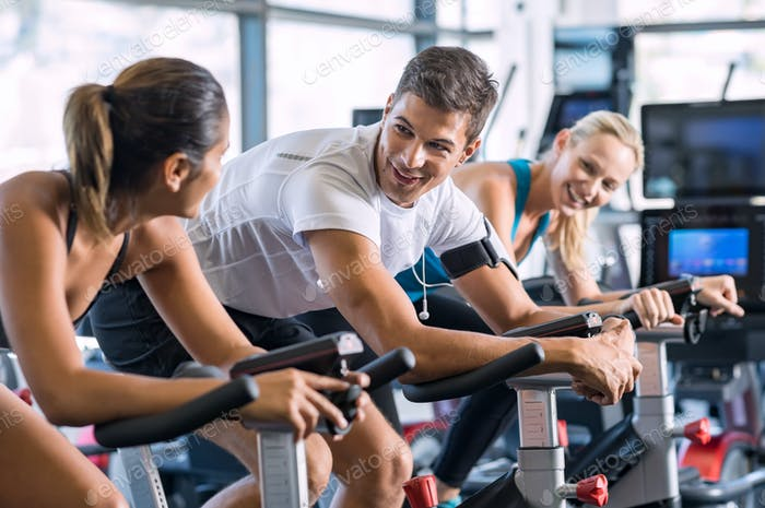 Fit people cycling at gym