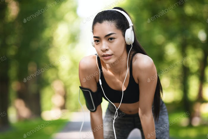 Portrait Of Tired Asian Jogger Girl Taking Breath After Jogging In Park