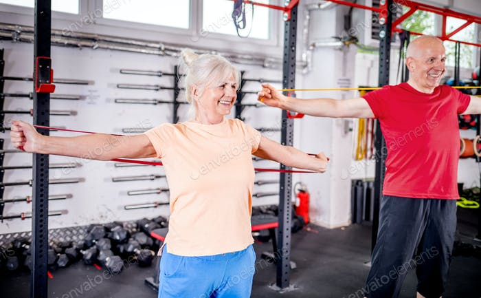 Senior people with resistance band doing exercises at the gym