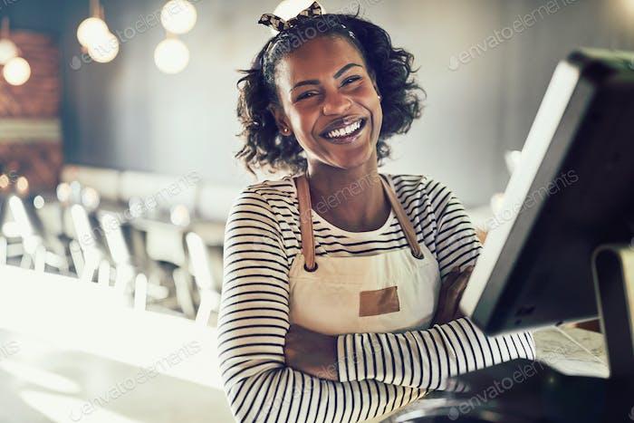 Junge afrikanische Kellnerin lacht während der Arbeit in einem trendigen Restaurant