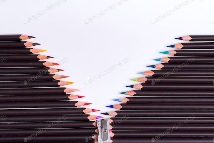 Decorative backdrop from colored pencils in the shape of opened zip on a white background