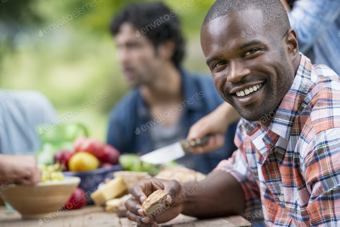 A summer party outdoors. A man smiling at the camera.