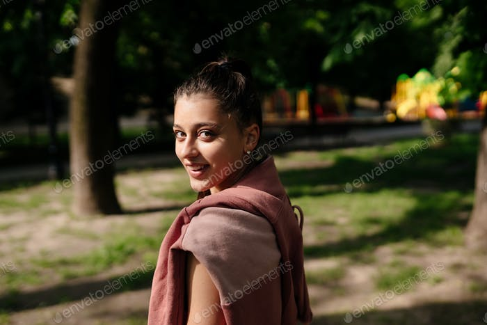 Young woman is resting after jogging in the park
