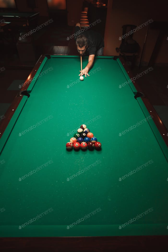 Player prepares to breaks a pyramid in billiards.
