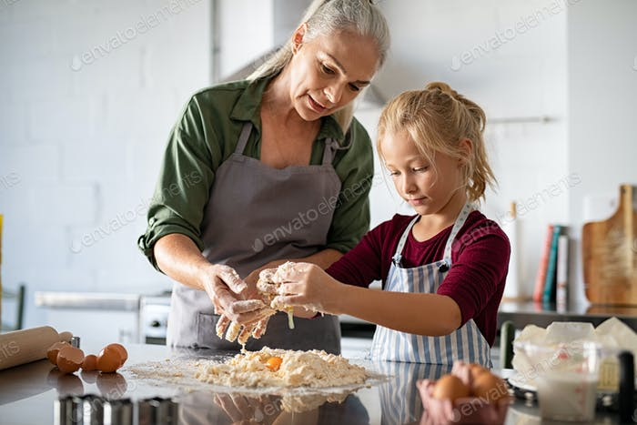 Grandmother and granddaughter preparing dough