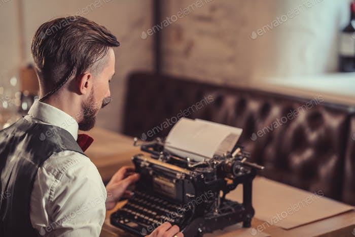 Young man typing on a retro typewriter
