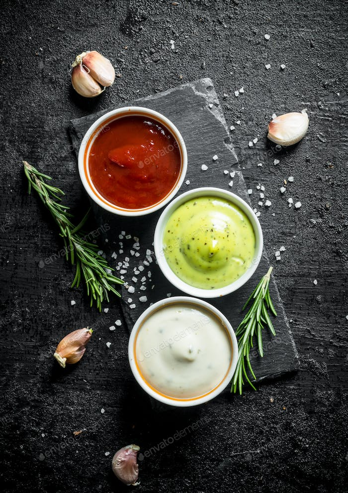 Delicious sauces guacomole, mayonnaise and ketchup with cloves of garlic and rosemary.